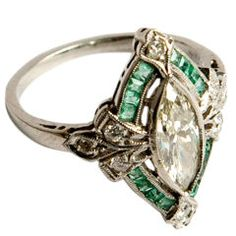 "1930s  The marquise-cut center diamond is surrounded by diamond ""leaves"" and channel-set emeralds. It is set in platinum"