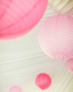 Large paper lanterns in alternating shades of pink hung from the peak of the tent
