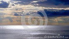 Clouds in blue skies over sunlit seas.