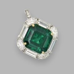 EMERALD AND DIAMOND PENDANT. The octagonal step-cut emerald weighing 10.57 carats, baguette and oval diamonds weighing a total of approximately 4.25 carats, the hinged pendant hook set with small round diamonds, mounted in platinum and 18 karat gold.
