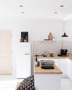 Jolie cuisine en total look blanc et bois, frigo rétro et crédence briques