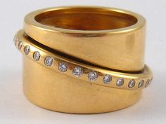 A French 18ct gold and diamond ring, the diamond set band rotating freely diagonally around the ring, signed Dinh Van, French hallmark and poincon, ring approx 14mm wide, size N, 19gms. Jean Dinh Van trained at Cartier for ten years circa 1950's.