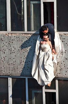 A man grabs a 22-year old woman after she tried to kill herself by jumping out of a window of a seventh-floor building in northeastern china's Jilin province. The bride cut her wrists and tried to commit suicide after her boyfriend broke up with her just before the marriage.
