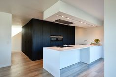 Moderne keuken met pivoterende deuren te Lommel. - De Groof Keukens Limburg
