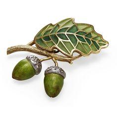 A plique-a-jour enamel brooch modelled as two acorns and an oak leaf, with green plique-a-jour enamel and diamonds.