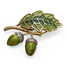 A plique-a-jour enamel brooch modelled as two acorns and an oak leaf, with green plique-a-jour enamel and diamonds.