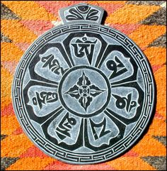 Om Mani Padme Hum mantra in Tibetan script, with double dorje in the center.