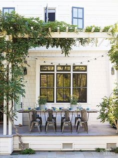 Pergola + Greenery. Table centered on bay window. Fireplace tucked to left.