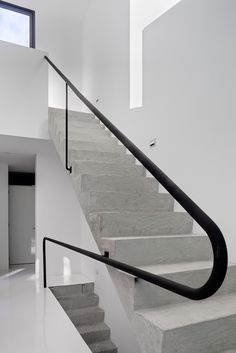 Concrete staircase + black steel handrail.