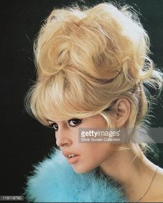 Headshot of Brigitte Bardot, French actress, model and singer, with a bouffant hairstyle and a blue boa in a studio portrait, against a black background, 1960.