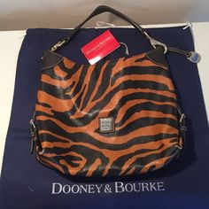 Dooney & Bourke Authentic Tiger Print Dooney & Bourke Authentic Tiger Print Small Sac Handbag Great Used Condition minor marks inside bottom corners have some wear see 2nd set of photos in additional listing overall Great Condition Very Sturdy Bag Original Price Tag & Dust Cover Included Dooney & Bourke Bags Shoulder Bags