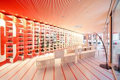 NYC Camper store designed by Japanese architect Shigeru Ban and New York-based architect Dean Maltz - red fins of parti-wall are angled to hide a shelving system for the shoes http://www.camper.com/en http://www.shigerubanarchitects.com/ http://www.dma-ny.com/