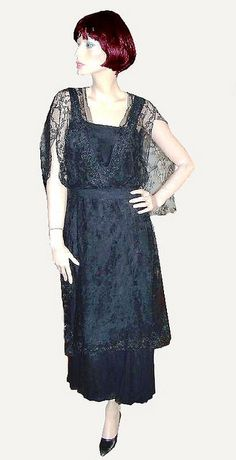 Late Edwardian Lace Overlay Dress  Gorgeous late Edwardian dress  with silk crepe underdress, with  chiffon flounce at hem of skirt. Overdress is metallic embroidered  black chantilly lace. Modified tabard  styling with back drape to   waistline.