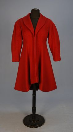 RARE CHARLES JAMES DESIGN COAT by WILLIAM POPPER, c. 1952. Claret wool with curved yoke, shawl collar and three quarter sleeve above princess seams, the wide flared skirt curving gracefully from above the knee in front to below the knee at back, black satin lining.