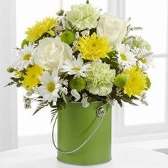 """The color of harmony, renewal and nature, our green metal paint can is ready to spread joy near and far. Fill it with green carnations, white roses, pompons and daisies for a vibrant display. Paint can (4.5"""" dia. x 5""""h with 3"""" dia. opening) - GREAT bouquet includes 13 stems. - Approximately 14""""H x 9""""W. - AWESOME bouquet includes 18 stems. - Approximately 15""""H x 11""""W. - STUNNING bouquet includes 24 stems. - Approximately 16""""H x 12""""W. Your purchase includes a FREE personalized gift message"""