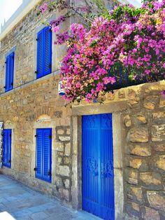 Bougainvillea, stone houses, blue door & windows of Bodrum, Turkey.
