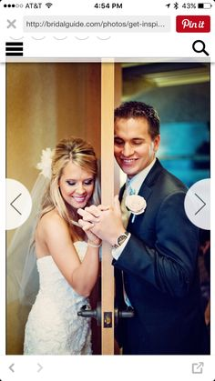 Bride and groom on either side of a door
