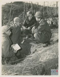 Robert Vermillion, United Press war correspondent (in leather jacket), gets front-line interview from Brazilian infantrymen in their fox-holes. L-R: Pvt. Edgar Vasques Rodrigues, and Pvt. Mario Feliciano Gauza, both from Rio de Janiero. At right is FEB Lt. Ruben Argolo, of Rio de Janeiro, who acted as interpreter. Italy. 11 December 1944