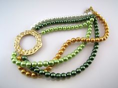 Necklace with green, gold and white pearls and golden hoop which is placed on the side of the neck.
