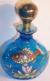 """Victorian Moser Glass Perfume Bottle Enameled Fish.  a deep ocean blue Bohemian Moser art glass perfume bottle with a hand painted raised enamel fish, lily pad and leaves. Measures 4 3/4"""" high and 3"""" wide. Stopper numbered """"11"""" in gold. Dates circa 1890."""