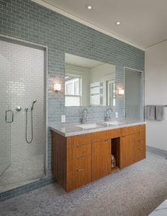 Wood vanity with marble countertop and gray tile backsplash