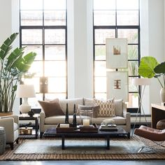 A neutral living room with a traveled feel. Art hung on windows.