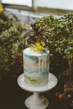 This single-tiered cake featuring muted watercolors and a dripping glaze is the perfect end to contemporary, seaside nuptials.