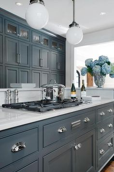 Amazing kitchen features dark gray center island adorned with cup pulls painted Porter's Paint Gray Bronze paired with Luce di Luna Quartzite Countertops fitted with a gas cooktop alongside a raised breakfast bar illuminated by white glass globe pendants facing a wall of floor to ceiling pantry cabinets.