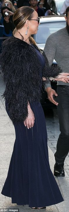 Diva style: The 45-year-old singer teamed her frock with a very glamourous black feather jacket and some stylish sunglasses