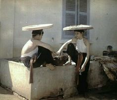 Two young Vietnamese women sitting on the edge of a cistern. Photo by Leon Busy, 1915