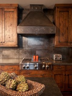 Rustic range hood made of metal. Bead board wood cabinet doors.