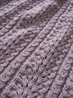 """Ostrich Plume blanket. Yarn is Calmer, color is """"Chiffon"""" discontinued.  Top edge of the lace didn't match the bottom edge (the bottom starts off with the pattern row, top finishes with the """"plain"""" Row 2 and dec row).  Instead of the dec row, I worked the patt row (Row 1) without yo in the cable sections. Then worked the 8 rows of garter st.  If I'd been willing to rip out the top border a third time, I would have slipped in a K2tog at each of those spots in the first garter row."""