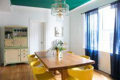 Meghan's gorgeous dining room with a pop of green on the ceiling. On the left is an antique pie cabinet that her aunt gave her. The yellow chairs are from West Elm.