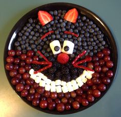 Alice in Wonderland Cheshire Cat fruit tray--grapes, blueberries, blackberries, strawberries, marshmallows, and twizzlers.