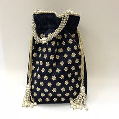 Potli bag in silk fabric. Base is made of gold metal beads, decorated with gold metal ambi motif and pearl drops. Zardozi Embroidery, Embroidery Bags, Unique Purses, Handmade Purses, Fabric Bags, Silk Fabric, Bridesmaid Bags, Ethnic Bag, Potli Bags