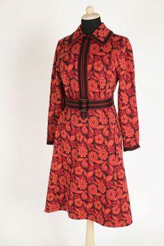"""Klänning skuren i ett fram-, två sido- och ett bakstycke. Påsydda långa ärmar. Knäppes fram med 38 cm lång, svart dragkedja. Byst- och axelveck. Snibbkrage. Två infällda fickor framtill. Mönstrat tyg på svart botten, med röda och orange blomsterslingor. Etikett: """"MMT Katja of Sweden"""""""