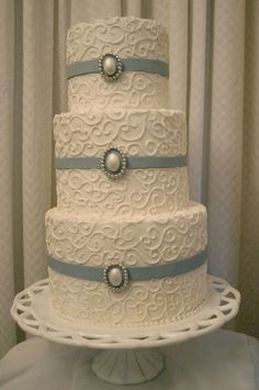 3 tier white scroll cake with fondant ribbon and edible pearl brooches