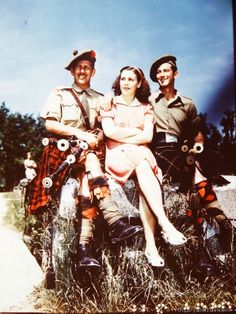 Two members of a Scottish regiment pose with a pretty Italian senorita in Milan, Italy. May 1945