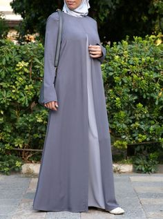Look effortlessly chic in this simple yet sophisticated abaya. Pretty and practical, its loose drape is as comfortable as it is modest. Clean lines and a smart contrasting double layered skirt add to the casual and carefree feel. Wear yours with a colorful hijab and fun purse for that perfect pop of personality.