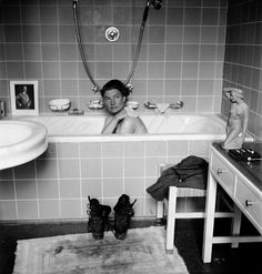Lee Miller in Hitler's apartment at 16 Prinzregent Note the combat boots on the bath mat now stained with the dust of Dachau; and a photograph of the previous owner of the flat propped on the edge of the tub. - 2245 | LeeMiller