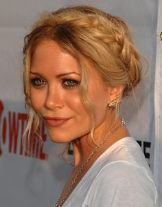Get Mary-Kate Olsen's chic milkmaid braid! 1) Rough up + texturize hair with product for better hold 2) Center part hair and create two pigtail braids, leaving out two one-inch sections at the front 3) Wrap one braid over the crown and pin behind the ear. Wrap the other braid over the crown, behind the first braid, then pin behind the ear. Pin lower sections of the braid with large French hair pins 4) Loosen braid and style front pieces 5) Complete the look with a hairspray for shine!