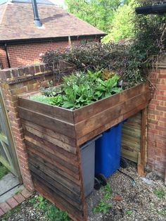 Pallet wheelie bin store with raised bed. Ship lapped boards and oxidised with vinegar and pallet nails.