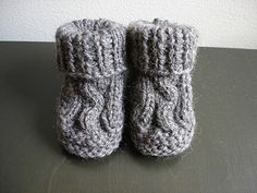 Easy baby booties knit on two needles feature a cable on the top of the bootie.