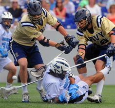 Navy's Michael Beggins (left) and Andy Tormey knock the ball away from Johns Hopkins midfielder Paul Rabil.