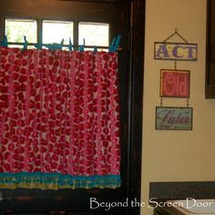 Fuchsia animal print cafe curtain lined with lime green chevron. Turquoise ball fringe.