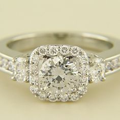 This semi mount is made in 14kt white gold and has a cushion diamond halo with an oval diamond on either side of a four prong set round stone with round brilliant diamonds channel set halfway down the shank. The oval diamonds total .24cts. of VS F-G quality and the rounds total .50cts. of VS F-G quality. The side view shows a detailed cutout weave. The center accommodates a 1ct. stone.  http://www.dbof.com/jewelry/levy-creations-14kt-white-gold-cushion-halo-round-semi-mount/#