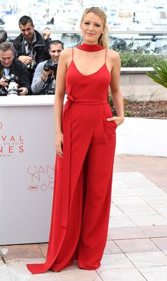 BLAKE LIVELY in a scarlet spaghetti-strap jumpsuit with a crossover train detail and matching scarf, plus a delicate gold Jennifer Meyer necklace, at the Café Society photocall.
