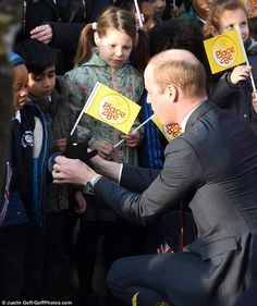Showing his paternal side, Prince William knelt down to help a youngster put on his glove...