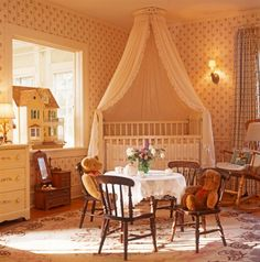 Traditional theme in a contemporary nursery, circa 2002. This nursery uses wallpaper, a ceiling-mounted bed crown, and a lace-covered table for a tea party.