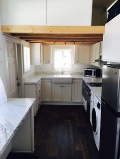 A beautiful, blue tiny house available for sale in Bellingham, WA. The home includes a kitchen fully outfitted with stainless steel appliances, two bedrooms,a bathroom, and a living/dining room area.